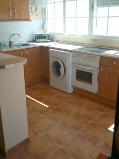 Cocina equipada con frigorífico, vitrocerámica, horno, lavadora,microondas, tostador y plancha