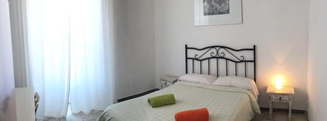 Big bedroom with double bed and little sofa.
