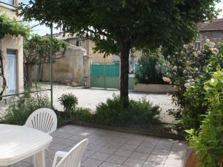 La terrasse et la cour. Au fond, le portail d'entrée et le portillon.