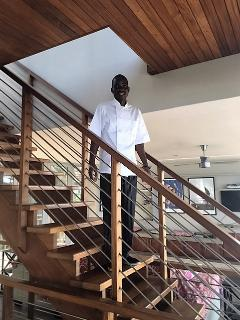Caretaker Axon on the staircase.  Stairs with hand rails lead up to bedrooms and down to bedrooms.