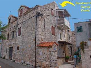 Apartment Livia, an old stone house with  bay view, Kaprije