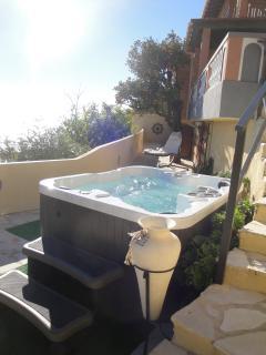 Le jacuzzi avec sa terrasse détente