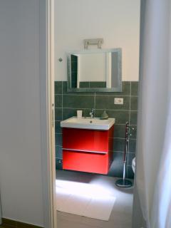 bathroom in bedroom with mega big shower, hair dryer, towels, soaps