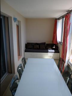 Loggia avec 1 tables, des chaises et 1 lit