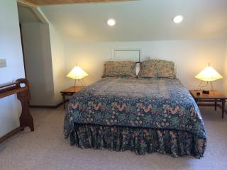 Master bedroom features organic latex Euro style queen mattress and lake views.