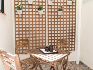 Patio / Terraza con mesa y sillas de madera. Pared emulando patio andaluz. Ideal para tomar un vino