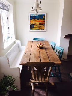 A rustic farmhouse table is at the centre of the dining area...