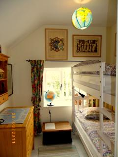 2nd bedroom with bunk bed, lego, toys and books overlooks gardens and leafy Abbey grounds