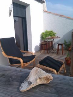 Terrasse avec bar, parasol, fauteuils de jardin, table à manger, éclairages