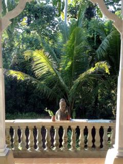 OVERLOOKING THE JUNGLE, A STATUE OF DEWI SRI - GODDESS OF RICE AND FERTILITY - ON THE TERRACE.