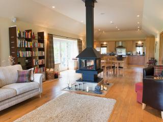 Large open plan living area with central wood burning stove and under floor heating