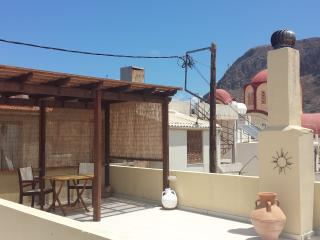 covered pergola & seating area on large roof terrace with views of the village church