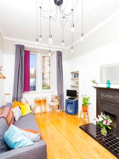 A bright Living room with 11+Ft ceilings, sofa bed (6Ft 7) & gas central heating