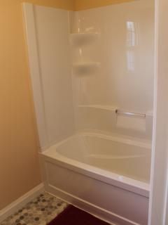 Brand new tub with shower surround.
