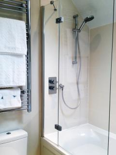 The crisp family bathroom boasts a double ended bath with shower overhead.
