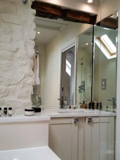 The handsome family bathroom's vanity area with exposed painted stone wall and original beams.