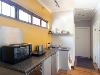 Kitchen with mini oven, Induction hotplate, fridge, microwave, kettle, toaster.