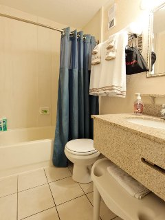 A private bathroom with shower, shower seat, bath tub, sink, towels, hair dryer, shampoo, and soap.