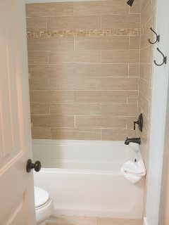Beautiful tile work in bath with plenty of towel hooks and rods . . . .