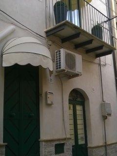 Facciata esterna della casa con balcone e due entrate