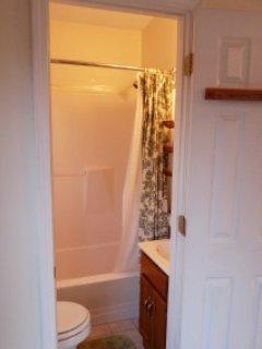 Small bathroom has a full tub.