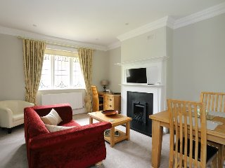 Lounge with gas fire, plasma TV & DVD, dining table, desk and comfortable sofa and chair.