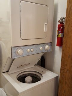 Washer/dryer unit behind folding doors in kitchen for small loads. fire extinguisher.