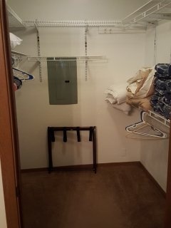 Shows walk in closet in bedroom with luggage rack, extra blankets, sheets for twin size air mattress