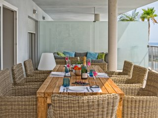 Terrace south with lounge and dining table, view to the sea and to the pool