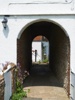 An archway in the middle of the sir georges place  leads to mill cottage - down a twitten.
