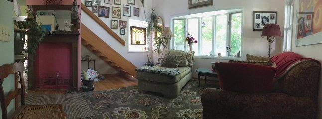 Panoramic view of living room and stairs.