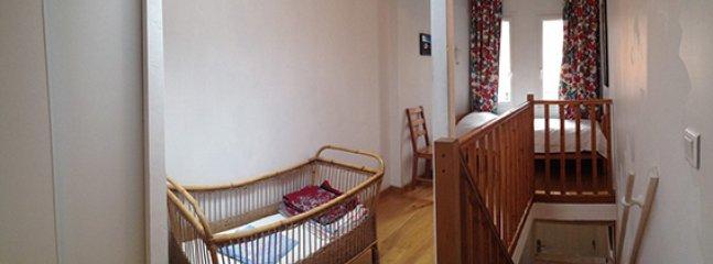 Premier étage avec un lit une place et un berceau. Une barrière de sécurité a été posée.