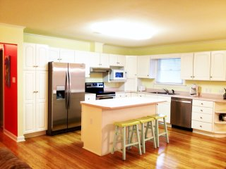Spacious open concept kitchen with stainless steel appliances, convection oven, and island seating
