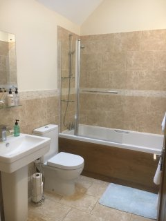House bathroom has a  shower over the bath and complimentary toiletries