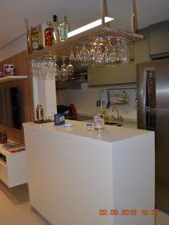 Balcão bar completo, taças,   copos especiais e bebidas disponíveis para compra.