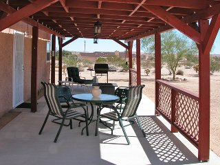 The covered patio is the perfect place to enjoy the desert scenery.
