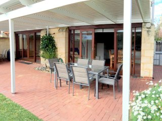 Great outdoor area with large table and BBQ. Two sets of double doors open to this area. Large lawn.