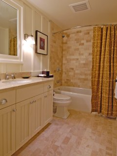 Secondary bathroom with marble counters, travertine floors and shower walls.