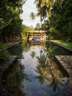 The outdoor pool with sunloungers and Ambalama
