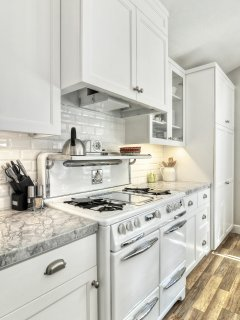 The kitchen is beautifully remodeled, with a restored antique stove.