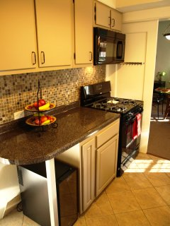 Kitchen with view of stove, microwave, ample counter top and wine fridge