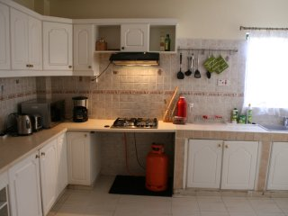 Kitchen from the entrance; four banner gas cooker with a hood.