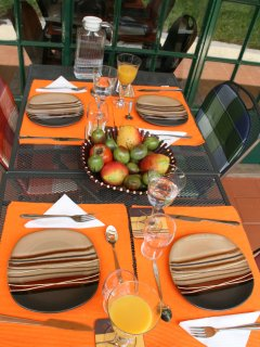 Breakfast setup for four on patio with passion and tomato fruits picked from garden, free to enjoy
