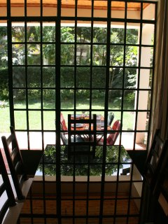 View of garden from dining area; permanent cover over patio