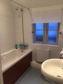 Family bathroom with bath and overhead shower, toilet and wash basin.