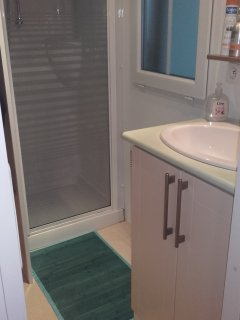 salle de bain avec douche 1 lavabo  etagéres de rangement