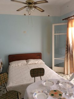 one end of big bedroom is with 1 double bed, ceiling fan and own tiny balcony