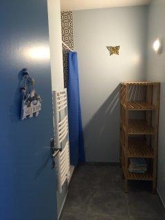Salle de bains avec douche, lavabo, sèche-serviette, étagères de rangement et lave-linge