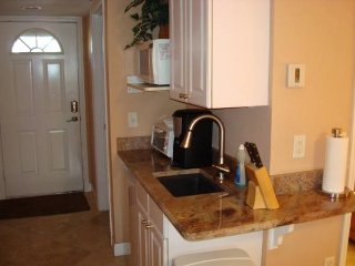 Mini kitchen has refrigerator, microwave, small toaster oven, coffee maker, blender, grill & skillet