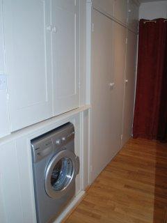 Wardrobe & dressing area with washing machine.
